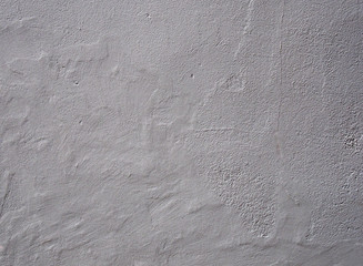 light grey rough textured wall background with an uneven worn surface with cracks and a weathered surface
