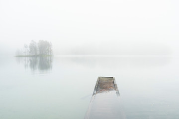 Reflection of trees and a pier sticking out of the water on a foggy day