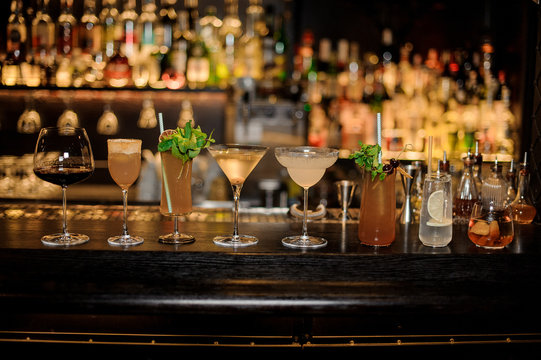 Many delicious cocktails in a line on the bar counter