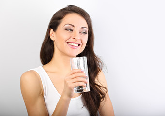 Positive happy woman with healthy skin and long curly hair drinking pure water on white background with toothy smile