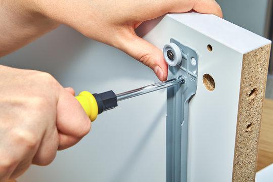Furniture assembler tightens screw in drawer slides.