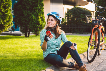 Man and city rolling bicycle, environmentally friendly transport. Beautiful young caucasian woman worker sitting resting on the grass uses a red mobile phone near an orange bicycle with a coryne.