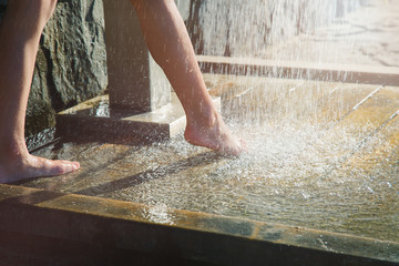 Child or little girl standing on wet wooden floor taking shower, low section, only legs