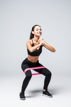 Young fitness woman doing squats with fitness loop band isolated on white background