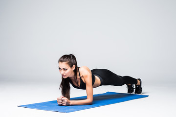 Concentrated beautiful fitness girl in sportwear exercising doing a plank over white background