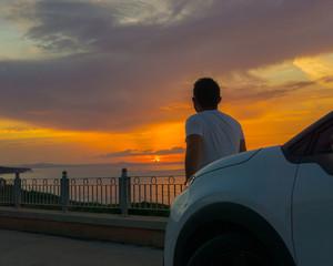 Hombre de espaldas disfrutando del paisaje con el mar de Cerdeña de fondo y el atardecer o amanecer.