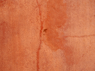 an old faded red cracked rough textured painted concrete wall background