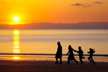 シルエットの四人家族が歩く夕日が沈む美しい海岸