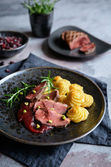 Duck breasts with Pommes Duchesse, cranberry sauce and pistachios
