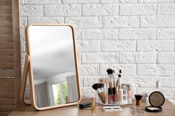 Makeup cosmetic products and tools on dressing table near brick wall with space for text