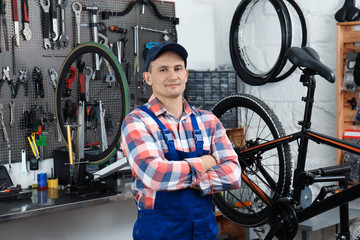Professional mechanic with bicycle in modern workshop