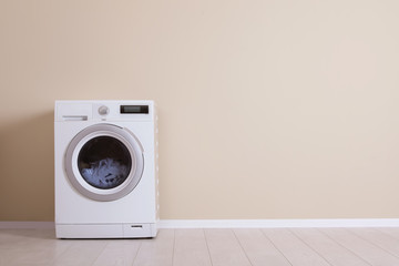 Washing machine near color wall, space for text. Laundry day