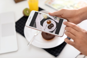 Food blogger taking photo of breakfast at home, focus on phone display