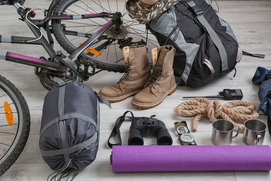 Sleeping bag, bicycle and set of camping equipment on wooden floor