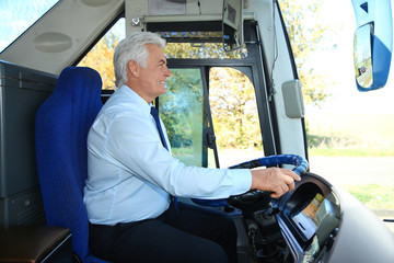 Professional bus driver at steering wheel. Passenger transportation