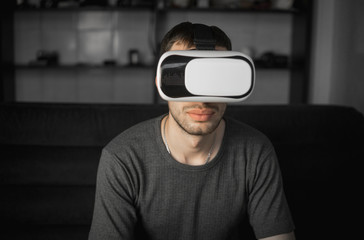 Young bearded man wearing headset of virtual reality in office sitting on a sofa.