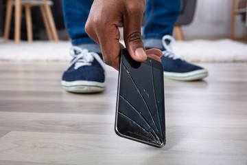 Man Picking Up Damaged Mobile Phone