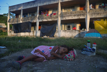 Nicole Giron, a five-year-old migrant girl from Honduras, part of a caravan of thousands traveling from Central America en route to the United States, sleeps on the floor outside of a derelict hotel used by migrants whilst they rest in Matias Romero