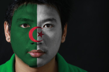 Portrait of a man with the flag of the Algeria painted on his face on black background, green and white, charged in the center with a red star and crescent.