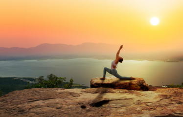 Photo on textile frame Yoga school Woman practice yoga on mountain with sunset or sunrise background