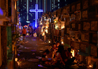 Filipino families visit the graves of their departed loved ones during All Saints Day in a public cemetery in Makati