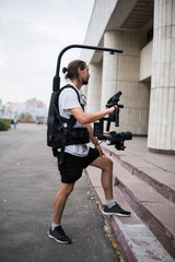 Professional videographer holding camera on 3-axis gimbal which mounted on easy rig. Videographer using steadicam. Pro equipment helps to make high quality video without shaking.