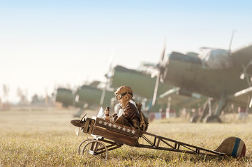 Fototapeta Portrait of the young aviator in a toy airplane child obraz