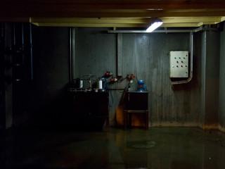 Industrial basement with wet floor. Dark gloomy ambient terror movie concept