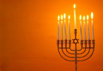 image of jewish holiday Hanukkah background with menorah (traditional candelabra) and candles.