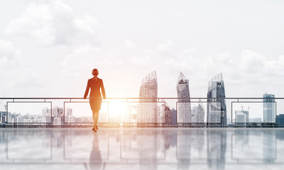 Sunrise above skyscrapers and businesswoman facing new day