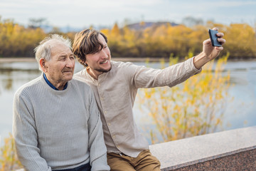 A man takes a selfie with an older man