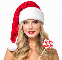 Beautiful  girl wearing santa claus clothes. Christmas Woman with a lollipop. Beauty Model Girl in Santa Hat isolated on White Background.
