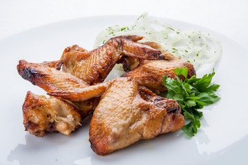 Grilled chicken wings on a white plate