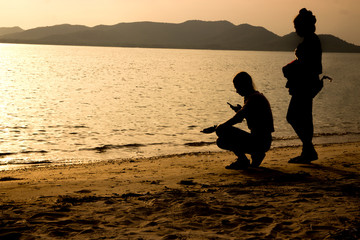 silhouette of people at the beach Beach activities The beauty of natural light at sunset.