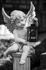 Closeup of stoned angel with lantern on tomb in cemetery