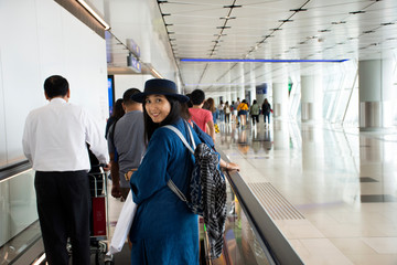 Travelers thai woman walking in terminal go to bus station at Hong Kong International Airport, Mainland China