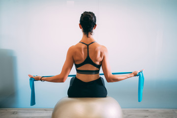 Young sporty attractive woman practicing pilates with resistance bands back sitting on fitness...
