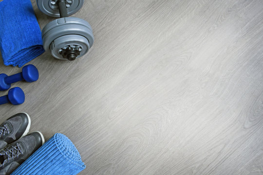 Sneakers, two blue dumbbells, a towel and a workout mat. Sport fitness items on light grey wooden background with empty text space. Active lifestyle, weight loss, body care concept. Top view.