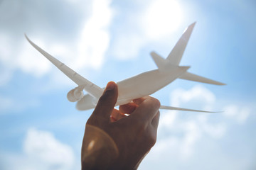 Hand holding toy airplane against blue sky with clouds.Travel inspiration trip flight.