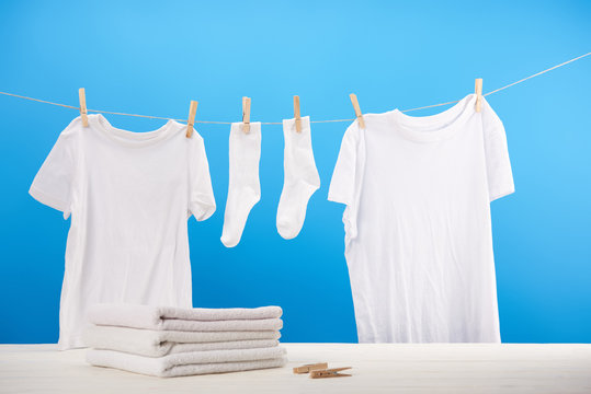 pile on clean towels, clothespins and white clothes hanging on rope on blue