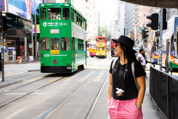 Thai woman walking go to bus station for passenger retro and vintage tram tour in Hong Kong, China