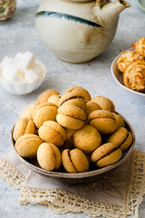 'Baci di dama': italian delicious cookies with chocolate and hazelnuts and topping on delicate background