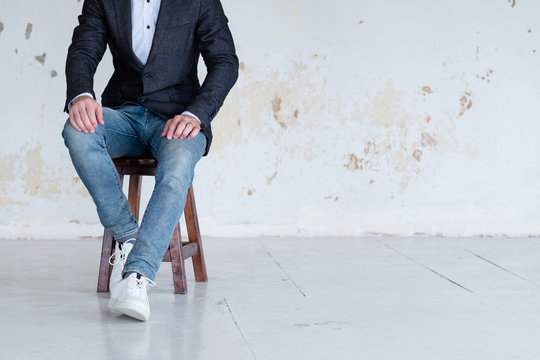 man in jacket and jeans sitting on a chair. confident business trainer or entrepreneur. smart casual dress code.