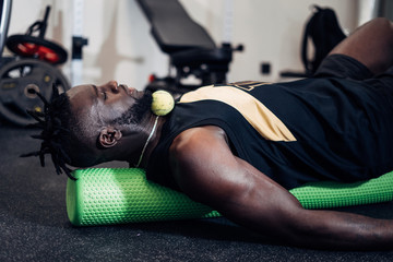 Black attractive strong man Doing an Exercise with Foam Roller on his Upper Back in a gym. Sport.