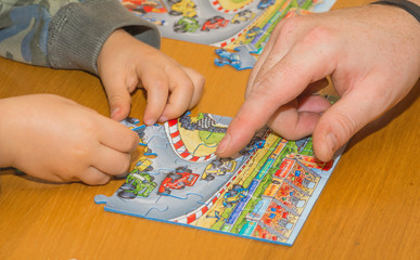 little kid playing with puzzles on wooden table together with parent, lifestyle people concept