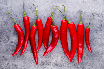 Chili cayenne pepper on grey background.