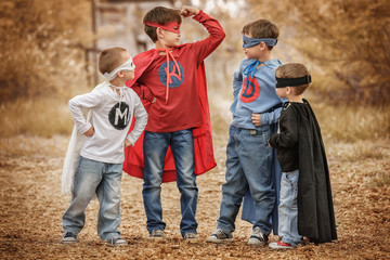 Four boys play a superhero in the playground