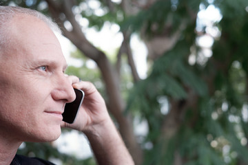 Profile portrait of attractive confident senior Caucasian man making phone call outdoors on blurred background