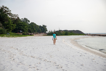 Lonely tourist on white sand beach by sea. Sole female tourist. Summer vacation on tropical island.