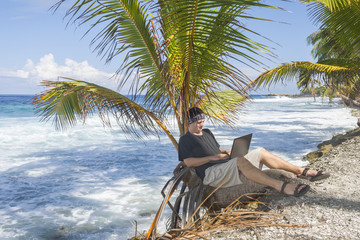 Man working on the beach. Attractive man with laptop seated in a palm tree on a tropical beach. Young man working on laptop computer on the tropical beach in a palm tree.